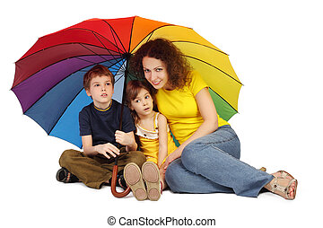 mother, daughter and son with big multicolored umbrella sitting isolated on white and looking at camera