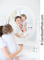 Mother, daughter applying make up - Young beautiful woman...