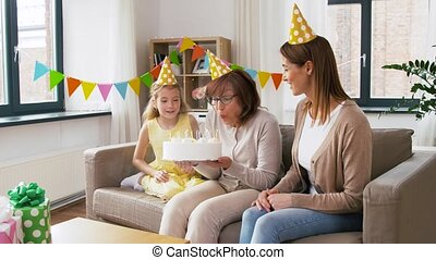 mother, daughter, grandmother with birthday cake - family,...