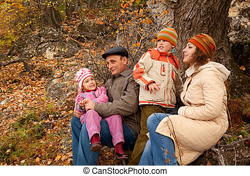 Mother, daughter, the son and the grandfather in the forest in autumn