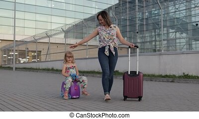 Caucasian mother and little daughter walking outdoors from international airport terminal. Woman carrying on wheels. Child rides suitcase. Girl and mom after departure from vacation, trip, holidays