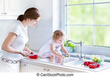 Mother, daughter washing vegetables - Young mother and her...