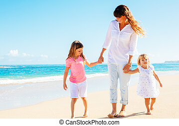 Mother daughters walking on the beach