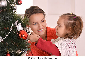 mother decorating christmas tree with daughter