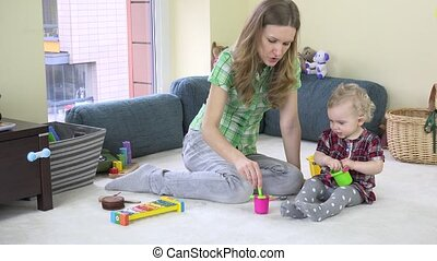 Mother develop her daughter imagination by eating invisible food from toy dish