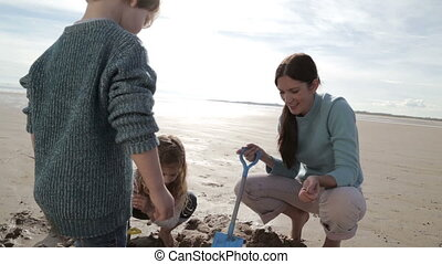 Mother Digging With Children on the Beach - A young mother...