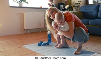 Mother does fitness with her little baby at home.