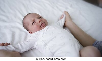 Mother doing gymnastics to her cute little baby on bed at home