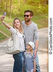 Mother doing selfie with her husband and little girl.