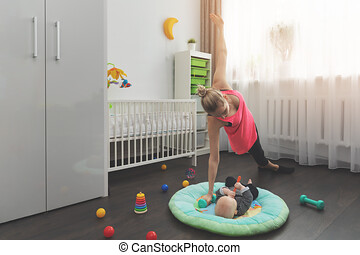 mother doing workout at home while babysitting