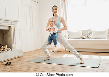 Mother doing yoga while holding her child on arms at home