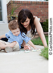 Mother Drawing With Chalk On Sidewalk With Son