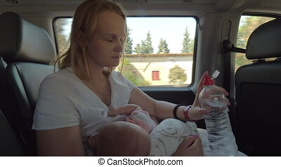 Mother drinking water and nursing baby in the car