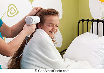 Mother drying her little girl's hair after bath