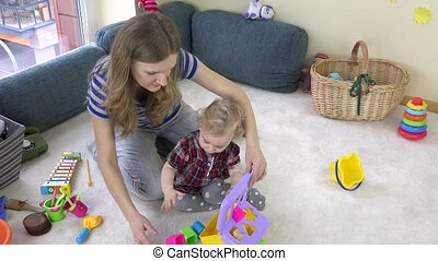 Mother educate little baby daughter with variety of functional developmental toys indoor. Baby room. Childhood. 4K