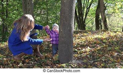 Mother embrace hug her baby daughter near tree trunk in autumn season park. 4K