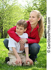 Mother embraces behind  son sitting on laps on grass in park in spring
