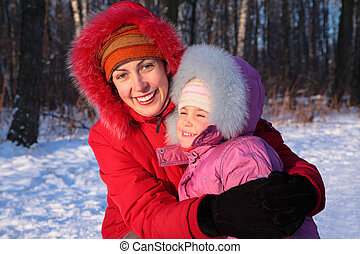 Mother embraces daughter in park in winter