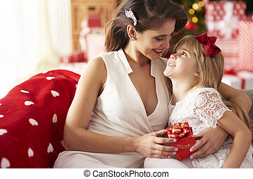 Mother embracing daughter and looking at her
