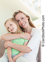 Mother embracing daughter on sofa