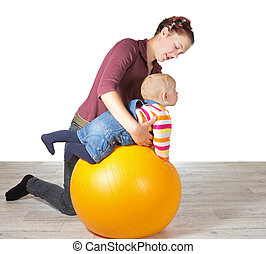 Mother exercising her young baby supporting it over a gym ...