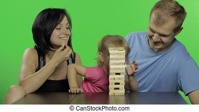 Mother, father and daughter play. Pulls wooden blocks from...