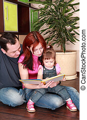 mother, father and little daughter in denim jumpsuit reads ...