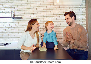 A happy family is playing at the table in the room.
