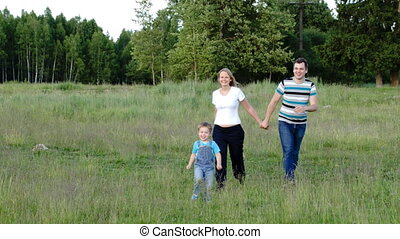 Mother, father and son walking on the meadow