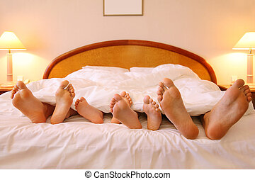 Mother, father and two children lie on bed with white sheets; focus on feet