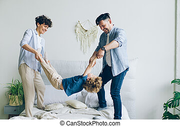 Mother father swinging child holding hands and feet then putting on bed at home