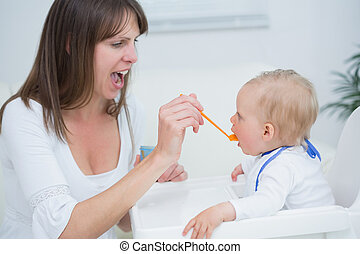 Mother feeding a baby while opening her mouth