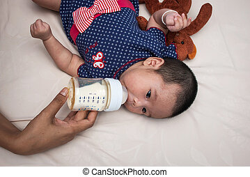 mother feeding a newborn baby with a bottle of milk