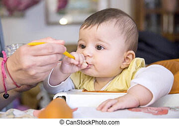 Mother feeding babe with spoon