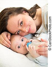 mother feeding baby boy by milk