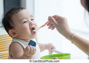 Mother feeding baby boy.