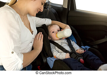 Mother feeding baby boy with milk on car back seat