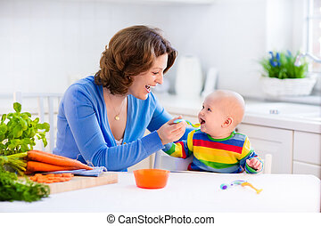 Mother feeding baby first solid food - Mother feeding child...