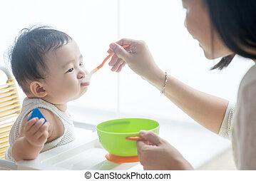 big baby eating young woman feeding an infant adult man in baby headwear. Black Bedroom Furniture Sets. Home Design Ideas