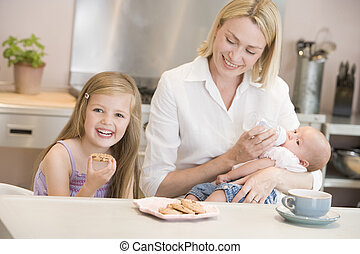 Mother feeding baby in kitchen with daughter eating cookies and smiling