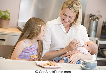 Mother feeding baby in kitchen with daughter eating cookies and