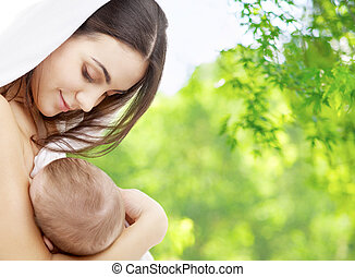 mother feeding baby over natural background