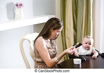 Mother feeding baby solid food