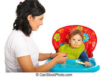 Mother feeding baby boy isolated on white background