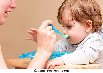 mother feeding baby with a spoon at the table.