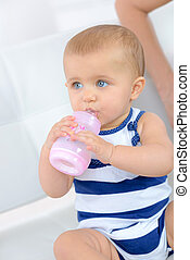 mother feeding baby with milk bottle closeup
