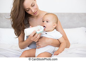 Mother feeding baby with milk bottle in bed at home
