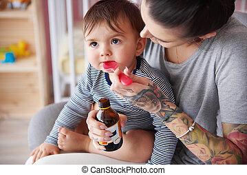 Mother feeding boy with medicine