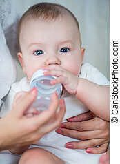 mother feeding by milk his baby infant from bottle