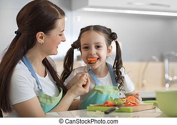 mother feeding child daughter vegetables in kitchen